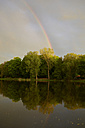 Germany, Schleswig Holstein, View of rainbow near Little lake at dusk - TKF000129