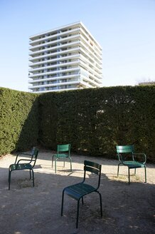 Germany, Bavaria, Munich, Chairs in garden with office building in background - ED000040