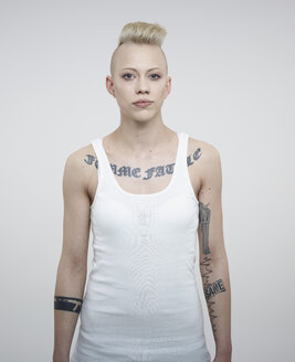 Portrait of young woman with tattoos against white background - RH000224