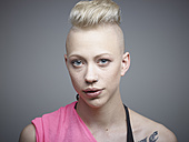 Portrait of young woman with tattoos against grey background, smiling - RH000203