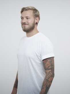 Young man with tattoos against white background, smiling - RH000198