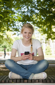 Germany, Berlin, Portrait of young woman sitting on bench with mobile phone, smiling - BFR000225