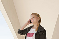 Germany, Berlin, Young woman tallking on mobile phone, smiling - BFR000230