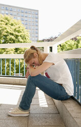 Germany, Berlin, Depressed young woman sitting on railing - BFR000231