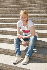 Germany, Berlin, Portrait of young woman sitting on stairs, smiling - BFR000232