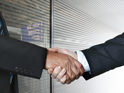 Businessmen shaking hands at airport, close up - STKF000281