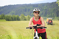 Germany, Mid adult woman with bicycle in forest - VT000011