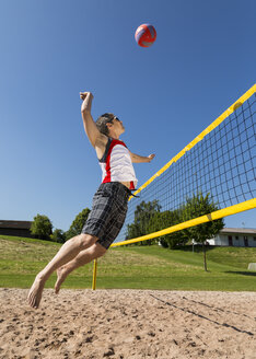 Germany, Mature man playing beach volleyball - STSF000017