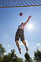 Germany, Mature man playing beach volleyball - STSF000031