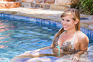 Young woman relaxing in swimming pool, smiling - ABAF000906
