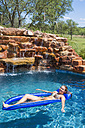 Young woman relaxing on float in swimming pool, smiling - ABAF000902