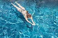 Young woman swimming in pool - ABAF000899