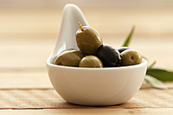 Spoon of olives on wooden table, close up - OD000036