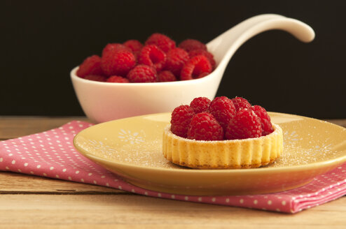 Spoon of raspberries with tartlet and napkin on wooden table, close up - OD000042