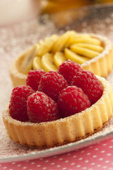 Banana and raspberry tartlets on plate, close up - OD000041