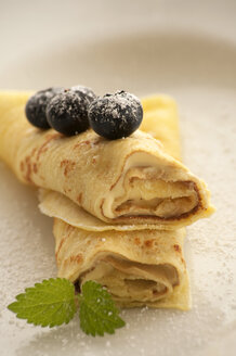 Crepe with custard and blueberries on plate, close up - OD000049
