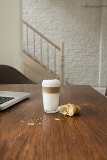 Croissant on table with drink and laptop - FMKYF000345