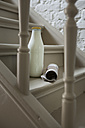 Milk bottle and newspaper on steps - FMKYF000334