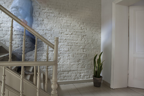 Mature man moving down staircase - FMKYF000330
