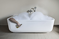 Mid adult man in bathtub with beer bottle - FMKYF000317
