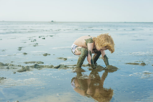 Germany, Schleswig Holstein, Boy playing in mud at beach - MJF000211