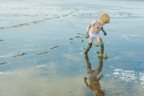 Germany, Schleswig Holstein, Boy playing in mud at beach - MJF000212