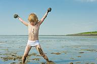 Germany, Schleswig Holstein, Boy playing in mud at beach - MJF000215