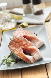 Raw salmon in plate with salt and pepper in background, close up - OD000081