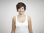 Portrait of young woman standing against white background, smiling - RH000229