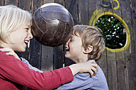 Germany, North Rhine Westphalia, Cologne, Boys playing with ball in playground, smiling - FMKYF000412
