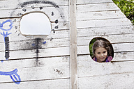 Germany, North Rhine Westphalia, Cologne, Portrait of girl peeking from hole, smiling - FMKYF000386