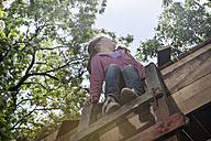 Germany, North Rhine Westphalia, Cologne, Girl sitting on steps at playground - FMKYF000390