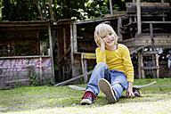 Germany, North Rhine Westphalia, Cologne, Portrait of boy sitting on skateboard, smiling - FMKYF000426