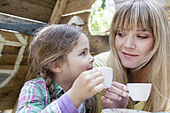 Germany, North Rhine Westphalia, Cologne, Mother and daughter drinking tea, smiling - FMKYF000368