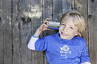 Germany, North Rhine Westphalia, Cologne, Portrait of boy listening to tin can phone, smiling - FMKYF000431