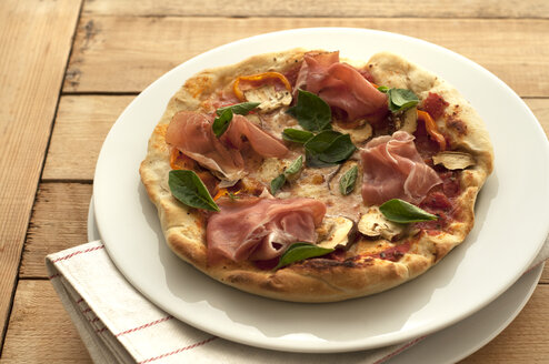 Plate of pizza with ham, basil, mushrooms and mozarella on table, close up - OD000095
