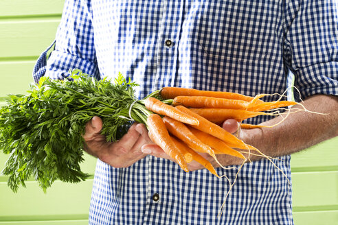 Mature man holding bunch of carrots against green background, close up - MAEF006883