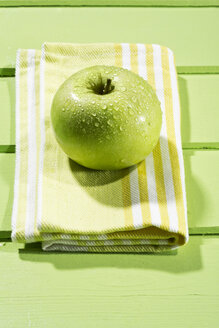 Granny smith with napkin on wodden table, close up - MAEF006852