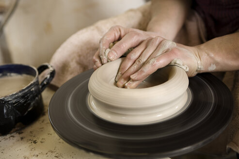 Germany, Bavaria, Mid adult woman working with clay on potter's wheel - RN001244