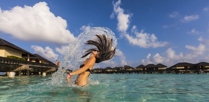 Maldives, Young woman splashing wet hair in lagoon - AMF000563
