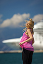 Greece, Young woman posing in front of cruise ship - AJF000015