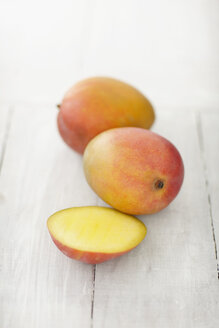 Mangoes on wooden table, close up - KSWF001162