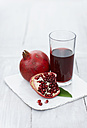 Pomegranates with juice on wooden table, close up - KSWF001159