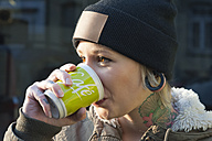 Germany, Freiburg, Young woman with tatoo drinking coffee, close up - LA000105