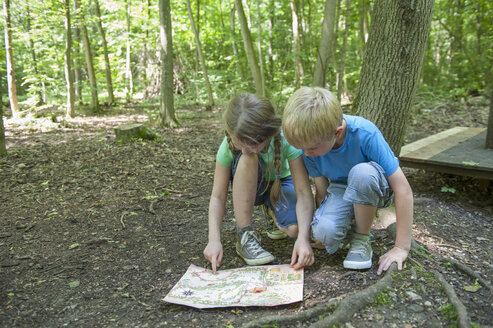 Germany, Bavaria, Munich, Friends reading treasure map in woods - NH001393