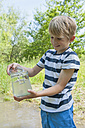 Germany, Bavaria, Munich, Boy filling water in glass jar at lake, smiling - NH001402