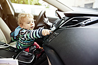 Germany, Bonn, Baby boy turning knob in car - MFF000537