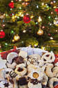 Christmas cookies in front of christmas tree, close up - SKF001325