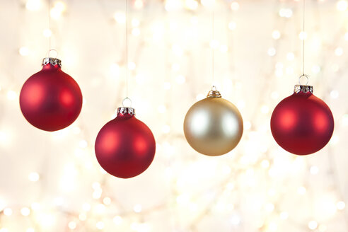 Christmas baubles hanging in front shiny background, close up - SKF001330