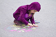 Germany, Girl drawing on street with chalk - SARF000050